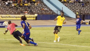 Reggae Boyz frontman Corey Burke slots a ball past Cayman Islands custodian, Ramon Sealy during a 4-0 rout at the National Stadium in Kingston.