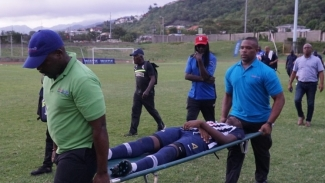 An injured Jamaica College player is taken from the field after lightening struck a football field during the Manning Cup.
