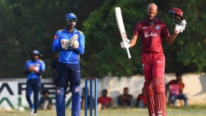 Roston Chase raises his bat as he gets to a century.
