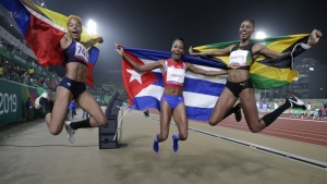 From left: Gold medalist Yulimar Rojas of Venezuela, left, bronze medalist Liadagmis Povea of Cuba, and silver medalist Shanieka Ricketts of Jamaica celebrate after the women's triple jump final during the athletics the Pan American Games in Lima, Peru, Friday, Aug. 9, 2019.