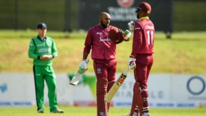 Windies batsman Sunil Ambris celebrates getting to three figures with teammate Roston Chase during a Tri-Nation Series game against Ireland on Saturday, May 11.